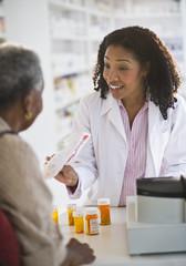 Pharmacist handing medication to woman