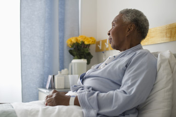 Black woman recovering in hospital bed