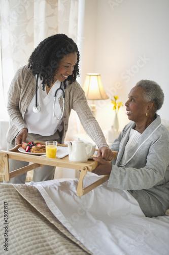 Nurse serving woman breakfast in bed