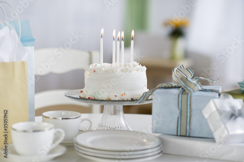 """Birthday cake, gifts with plates and cups"""