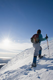 Hispanic woman snowshoeing up hill