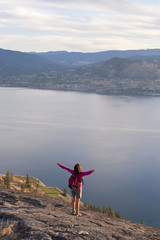 Hispanic hiker standing on cliff over lake