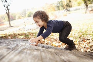 Mixed race girl climbing on rock