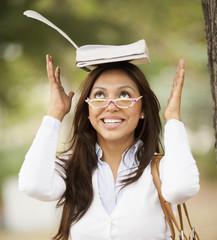 Hispanic woman balancing book on her head