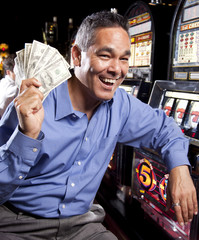 Excited mixed race man holding winnings in casino