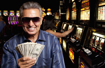 Excited Hispanic man holding winnings in casino