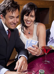 Couple enjoying cocktails and gambling in casino