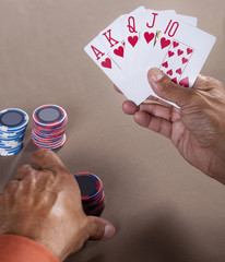 Hispanic man playing winning hand of poker