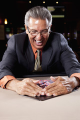 Excited Hispanic man gathering gambling chips