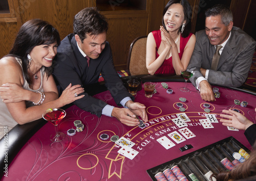 Couples enjoying cocktails and gambling in casino