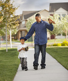 Father and son walking with baseball glove and bat