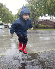 Caucasian boy jumping in rain puddle