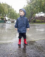 Caucasian boy standing in rain