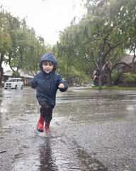 Caucasian boy splashing in rain puddle