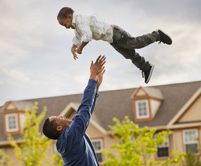Father throwing son into the air