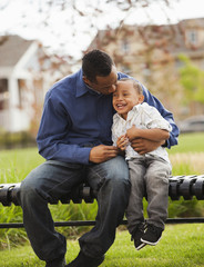 Father and son sitting together on park bench