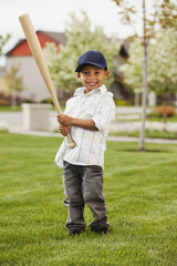Mixed race boy playing baseball in grass