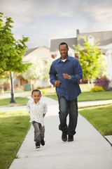 Father and son running on sidewalk