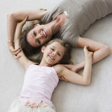 Caucasian mother and daughter laying on floor
