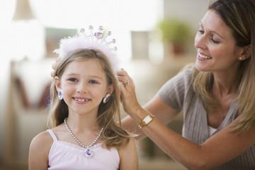 Caucasian mother adjusting tiara on daughter
