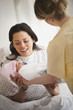 Nurse handing mother newborn baby girl