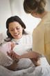 Nurse handing mother newborn baby girl