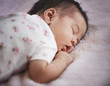 Mixed race newborn baby girl sleeping