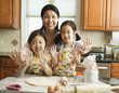Asian mother and daughters baking in kitchen