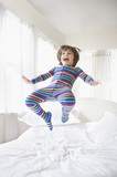 Caucasian boy jumping on bed