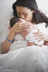 Mother in hospital bed holding newborn baby girl