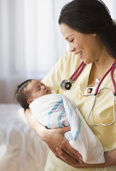 Nurse holding newborn baby girl