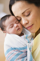 Mother hugging newborn baby girl