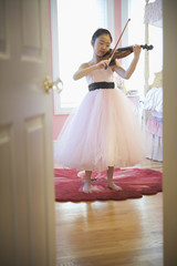 Asian girl in elegant dress playing violin