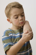 Caucasian boy looking at bandage on elbow