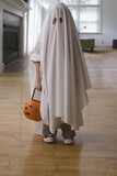 Caucasian boy dressed in ghost costume holding jack o'lantern