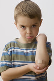 Pouting Caucasian boy with bandage on elbow