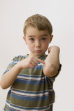 Caucasian boy pointing to bandage on elbow