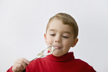 Caucasian boy eating batter from beaters