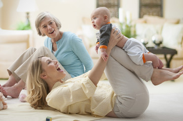 Caucasian grandmother and mother playing with baby boy