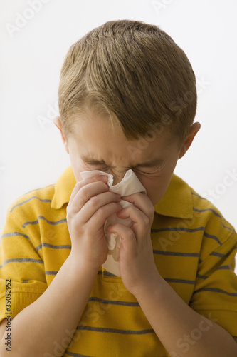 Caucasian boy blowing nose