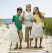 Caucasian children picking up litter from beach