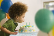 Mixed race boy blowing out birthday candles