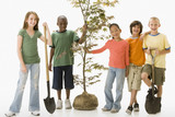 Children standing together with sapling tree and shovels