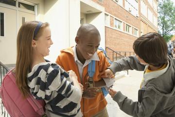 School boy teasing friend outdoors