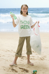 Caucasian girl picking up litter from beach