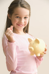 Caucasian girl putting coin into piggy bank