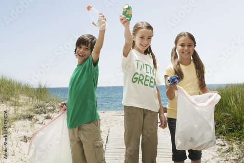 Caucasian children picking up litter from beach