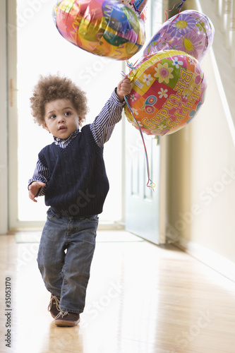 Mixed race boy holding birthday balloons
