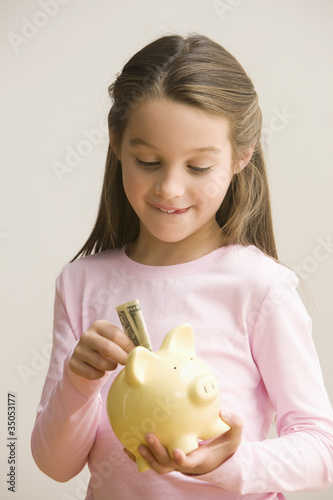 Caucasian girl putting money into piggy bank