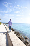 Hispanic man walking on wall near ocean